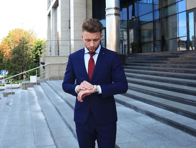 Biznesmen czeka na swojego kolegi na zewnątrz patrząc na zegarek.