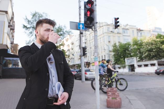 Biznesmen czeka na zielone światło sygnalizacji świetlnej i pije kawę.