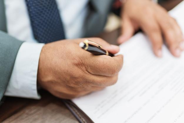 Biznesmen człowiek podpisuje dokumenty za pomocą pióra co podpis siedzi przy stole.