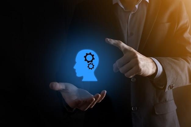 Biznesmen człowiek posiadający ikonę człowieka z biegami w głowie. sztuczna inteligencja. postęp technologiczny. robot. kontur symbolu.