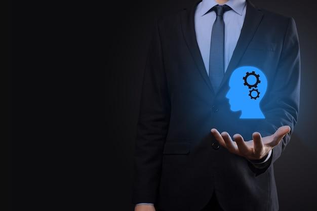 Biznesmen człowiek posiadający symbol człowieka z biegami w głowie. sztuczna inteligencja. postęp technologiczny. robot. symbol konturu.