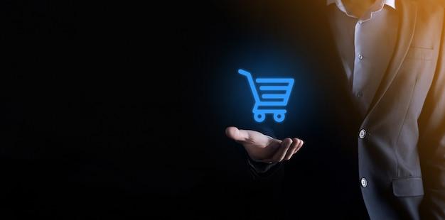 Biznesmen człowiek posiadający wózek na zakupy wózek mini wózek w biznesowym interfejsie płatności cyfrowych.