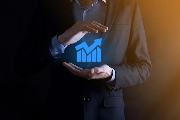 Biznesmen człowiek posiadający wykres z dodatnim wzrostem zysków. zaplanuj wzrost wykresu i wzrost pozytywnych wskaźników wykresu w swoim biznesie.bardziej opłacalny i rosnący.