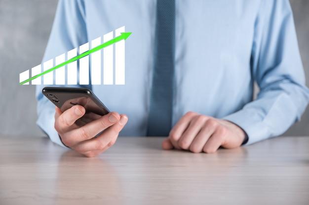 Biznesmen człowiek posiadający wykres z dodatnim wzrostem zysków. zaplanuj wzrost wykresu i wzrost pozytywnych wskaźników wykresu w swojej firmie.bardziej opłacalny i rosnący