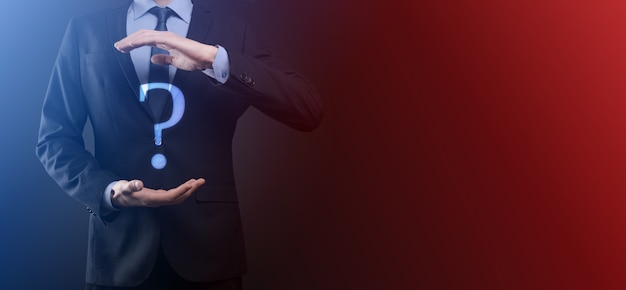 Biznesmen człowiek ręka trzymać interfejs znaki zapytania znak sieci web. zadaj pytanie online, koncepcja faq, co gdzie, kiedy, jak i dlaczego, szukaj informacji w internecie.