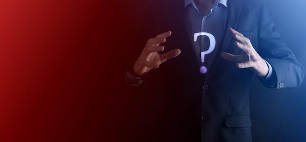 Biznesmen człowiek ręka trzymać interfejs znaki zapytania znak sieci web. zadaj pytanie online, koncepcja faq, co gdzie, kiedy, jak i dlaczego, szukaj informacji w internecie