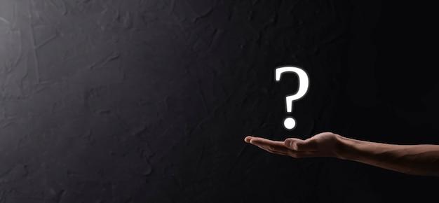 Biznesmen człowiek ręka trzymać interfejs znaki zapytania znak sieci web. zadaj pytanie online, pojęcie faq, co gdzie, kiedy, jak i dlaczego, szukaj informacji w internecie.
