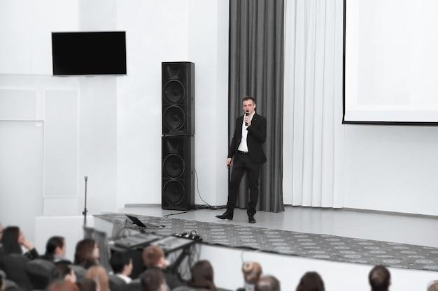 Biznesmen człowiek stojący na scenie podczas konferencji prasowej. pomysł na biznes