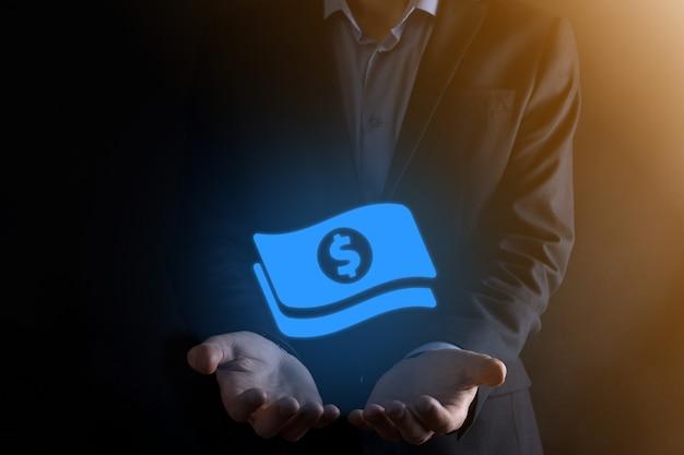 Biznesmen człowiek trzyma ikonę monety pieniędzy w jego ręce. rosnące pojęcie pieniędzy na inwestycje biznesowe i finanse. usd lub dolar amerykański na ciemnej ścianie.