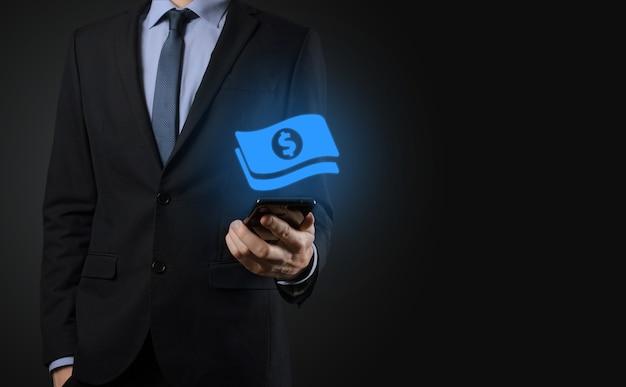 Biznesmen człowiek trzyma ikonę monety pieniędzy w jego ręce. rosnące pojęcie pieniędzy na inwestycje biznesowe i finanse. usd lub dolara na ciemnym tle.