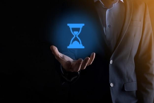 Biznesmen człowiek trzyma w ręku ikona klepsydry. czas upływa. przypomnienie do działania. pomysł na biznes. elementy do projektowania.