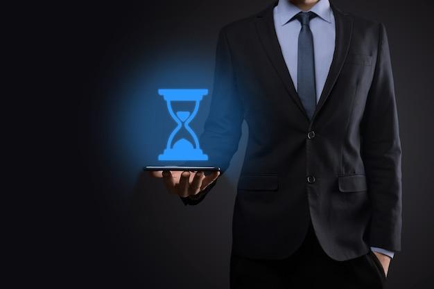 Biznesmen człowiek trzyma w ręku ikonę klepsydry. czas upływa. przypomnienie do działania. pomysł na biznes. elementy do projektowania.