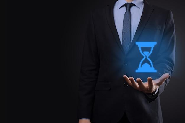 Biznesmen człowiek trzyma w ręku ikonę klepsydry. czas upływa. przypomnienie o działaniu. pomysł na biznes. elementy do projektowania.