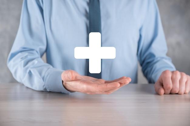 Biznesmen, człowiek trzyma w ręku oferują pozytywne rzeczy, takie jak zysk, korzyści, rozwój, csr reprezentowany przez znak plus. ręka pokazuje znak plus.