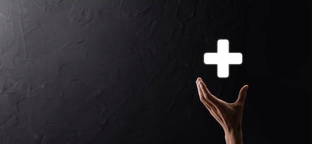 Biznesmen, człowiek trzyma w ręku, oferuje pozytywne rzeczy, takie jak zysk, korzyści, rozwój, csr reprezentowany przez znak plus. ręka pokazuje znak plus