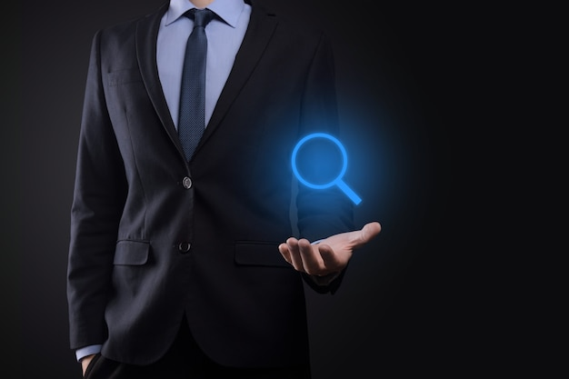 Biznesmen, człowiek trzymać w dłoni ikonę lupy. koncepcja biznesu, technologii i internetu