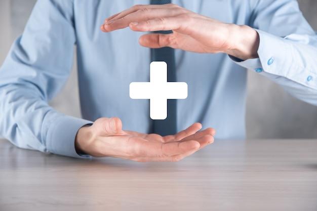 Biznesmen, człowiek trzymany w ręku oferuje pozytywne rzeczy, takie jak zysk, korzyści, rozwój, csr reprezentowane przez znak plus
