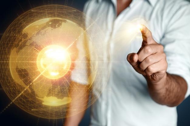 Biznesmen człowiek wskazuje na hologram planety ziemia. globalizacja, sieć, szybki internet, nowe technologie w komunikacji. kopiowanie miejsca mieszane media.
