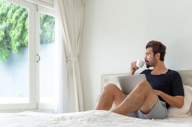Biznesmen czuje się szczęśliwy, pijąc kawę podczas pracy w domowym biurze