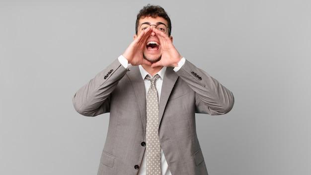 Biznesmen czuje się szczęśliwy, podekscytowany i pozytywnie nastawiony, wydając wielki okrzyk z rękami przy ustach, wołając