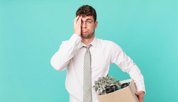 Biznesmen czuje się znudzony, sfrustrowany i senny po męczącym, nudnym i żmudnym zadaniu, trzymając twarz dłonią. koncepcja zwolnienia