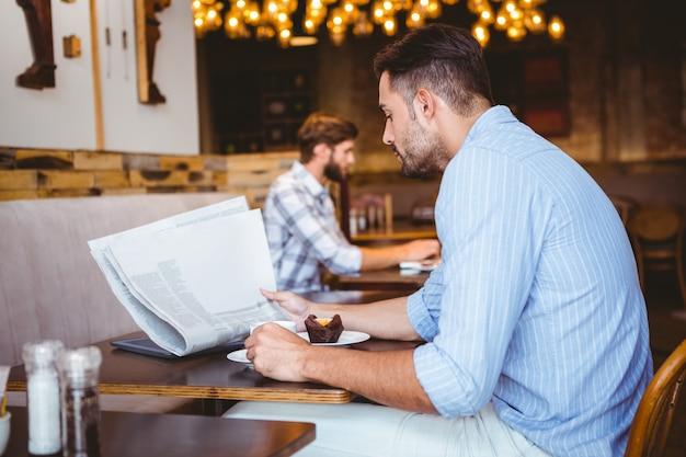 Biznesmen czyta gazetę podczas jedzenia