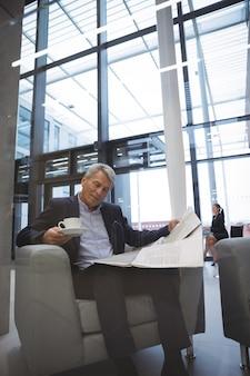 Biznesmen czytanie gazety mając kawę