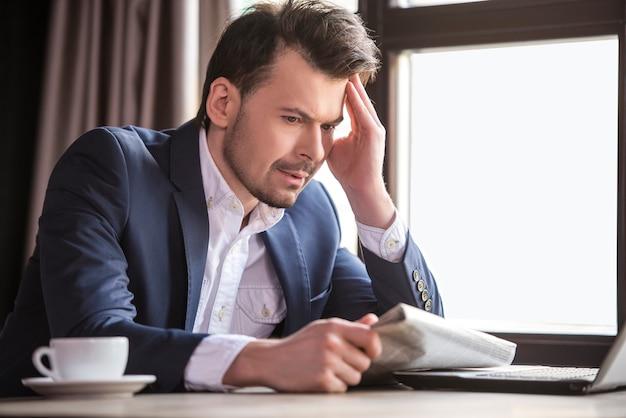 Biznesmen czytanie gazety w restauracji.