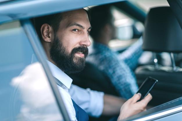 Biznesmen czytanie wiadomości sms na swoim smartfonie