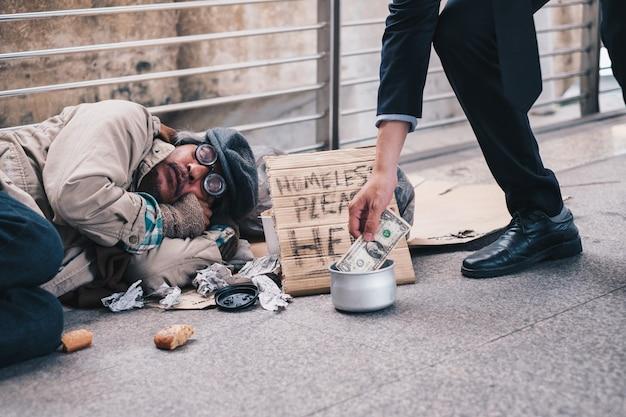 Biznesmen daje darowiznę w gotówce ze śpiącym starym bezdomnym