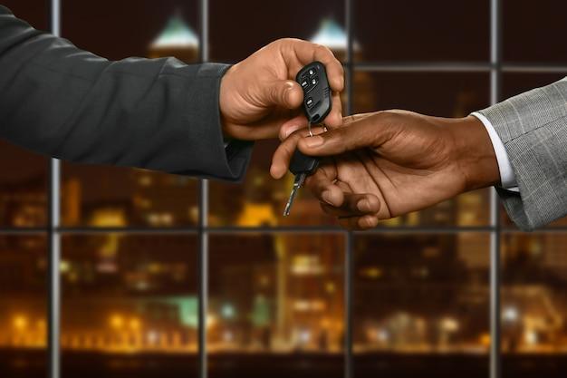 Biznesmen daje kluczyk od samochodu. mężczyźni przekazujący klucz w nocy. gotowy na jazdę próbną. znak zaufania.