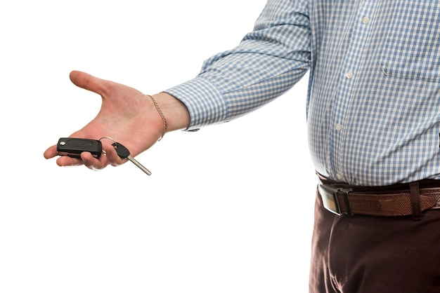 Biznesmen daje kluczyki do samochodu na białym tle na białej ścianie