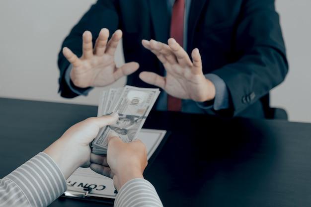 Biznesmen daje łapówkę urzędnikom państwowym, którzy podnoszą rękę, odmawiając koncepcji pieniędzy na przeciwdziałanie przekupstwu