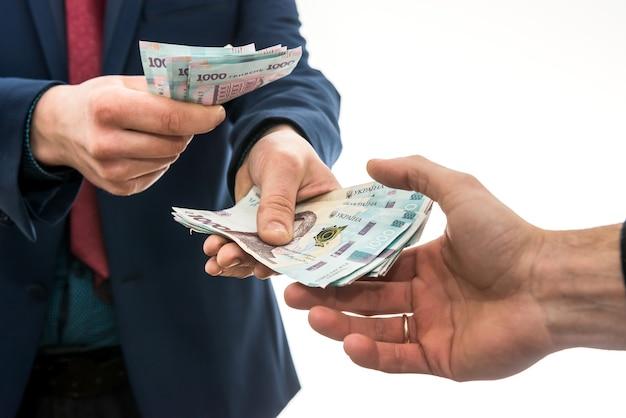 Biznesmen daje lub bierze łapówkę. hrywna ukraińska, nowe banknoty 1000 hrywien. zapisz lub koncepcja korupcji.