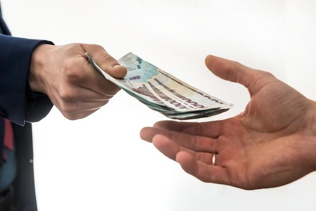 Biznesmen daje lub bierze łapówkę pieniędzy. hrywna ukraińska, nowe banknoty o wartości 1000 hrywien. zapisz lub korupcja.