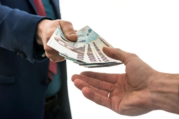 Biznesmen daje lub bierze łapówkę pieniędzy