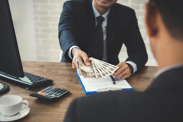 Biznesmen daje pieniądze partnerowi, jenowi japońskiemu, po uzgodnieniu