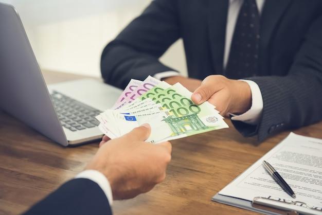Biznesmen daje pieniądze swojemu partnerowi, euro banknoty, podczas gdy robić kontraktowi