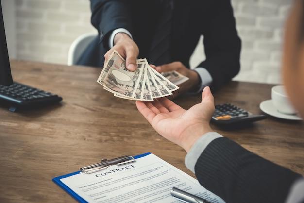Biznesmen daje pieniądze swojemu partnerowi, japońskiego jenu banknoty, podczas gdy robić kontraktowi
