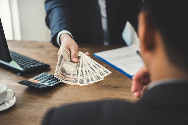 Biznesmen daje pieniądze swojemu partnerowi, japońskiemu jenowi
