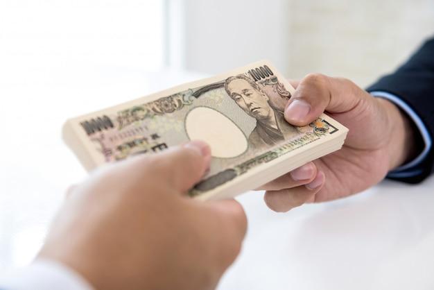 Biznesmen daje pieniądze swojemu partnerowi w postaci jena japońskiego