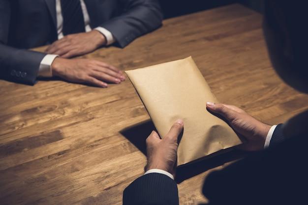 Biznesmen daje pieniądze w kopercie jego partner w zmroku