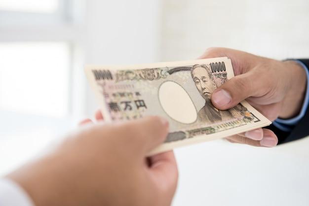 Biznesmen daje pieniądze w postaci japońskiego jena waluty