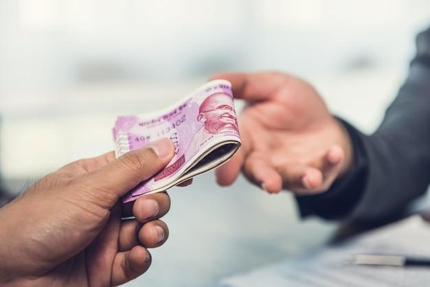 Biznesmen daje pieniądze, waluta rupii indyjskiej, partnerowi hs