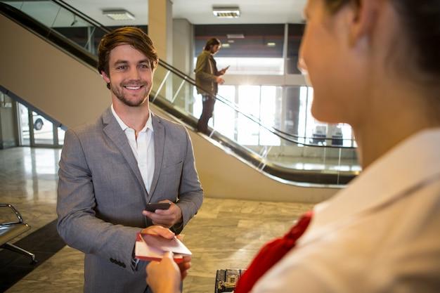Biznesmen daje swoją kartę pokładową żeńskiemu personelowi przy odprawy biurku