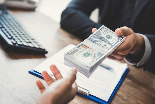 Biznesmen daje swojemu partnerowi pieniądze, dolary amerykańskie, podczas gdy robi kontraktowi