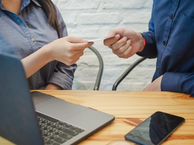 Biznesmen daje wizytówce bizneswoman w biurze.