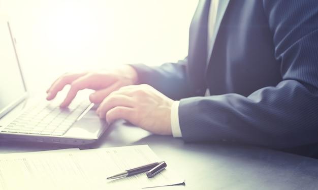 Biznesmen dokonuje transakcji online. handel na giełdzie przez internet. kierownik pracuje przy laptopie w biurze.
