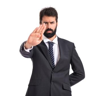 Biznesmen dokonywania znak stopu na bia? ym tle
