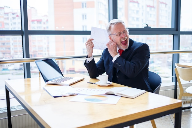 Biznesmen dorosły mężczyzna pracuje nad nowym projektem i patrząc na wykresy wzrostu zapasów. siedzi przy dużym oknie przy stole. patrzy na ekran laptopa i pije kawę.